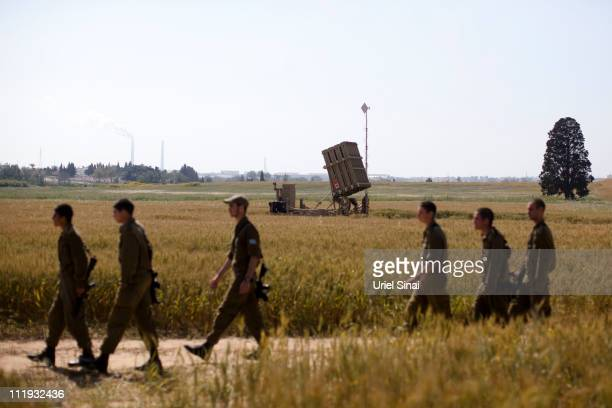 Israeli soldiers walk past the Iron Dome missile system on April 9, 2011 in Ashkelon, Israel. Tension is rising along the Israel-Gaza Border as...
