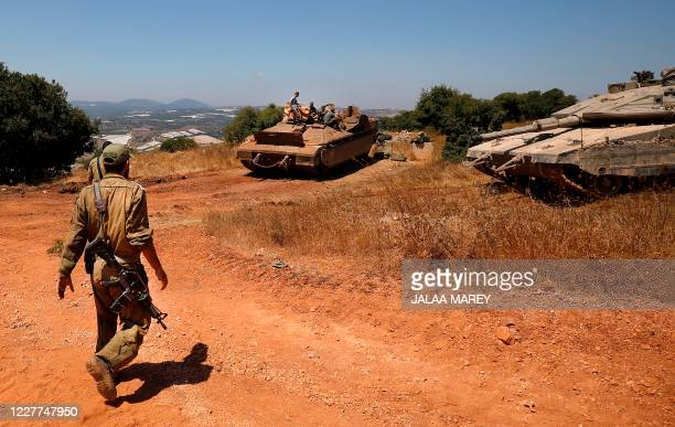 Israeli soldiers walk towards a Namer IFV and Merkava battle tank near the town of Avivim in northern Israel along the border with Lebanon on July...