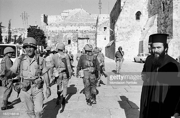 Israeli soldiers walking in the square of the Basilica of the Nativity watched by two popes in the Six Day War Bethlehem June 1967