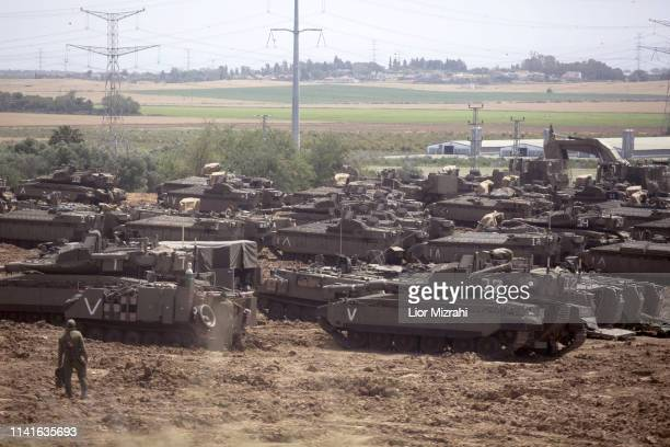 Israeli soldiers walks in front of a Merkava tanks stationed near the border with the Gaza Strip on May 6 2019 in Mavkim Israel Palestinian leaders...