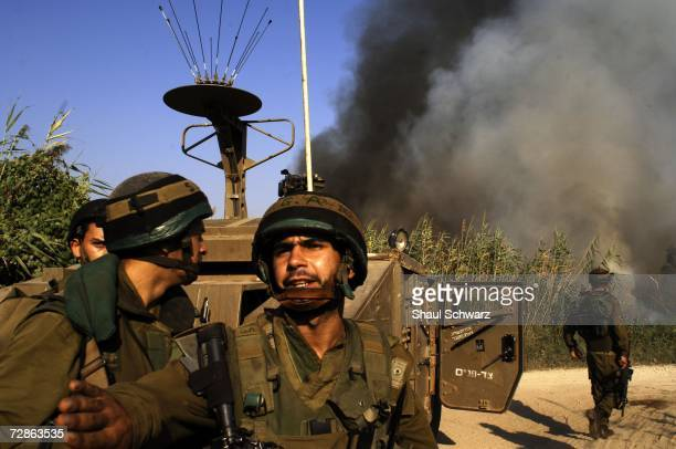 Israeli soldiers watch a fire that broke out after a rocket landed from Lebanon and fell near the northern Israeli town of Kiryat Shmona 18 July 2006...
