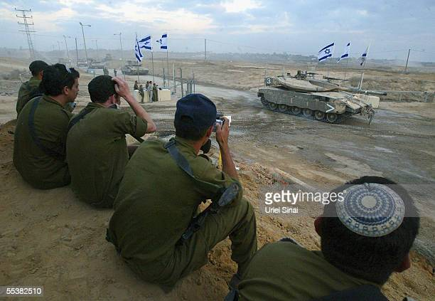 Israeli soldiers watch as an Israeli armored convoy leaves the Gaza Strip September 12 2005 through the Kissufim crossing between Israel and the Gaza...