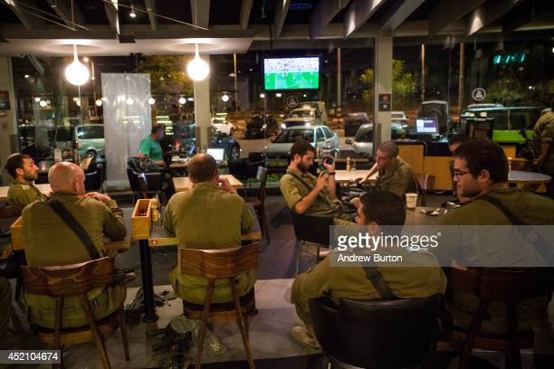 Israeli soldiers watch the 2014 World Cup final match between Germany and Argentina in a cafe on the sixth day of Israel's operation 'Protective...