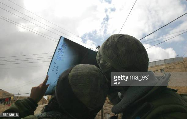 Israeli soldiers watch the partial eclipse of the sun using an old X-ray in the divided West Bank town of Hebron, 29 March 2006. The eclipse, caused...