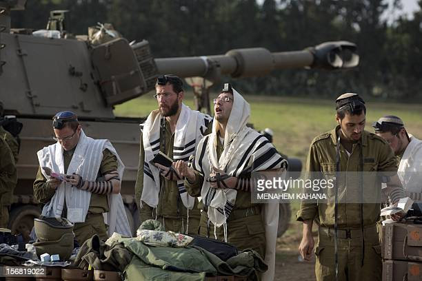 Israeli soldiers wearing 'Tallit' and 'Tefilin' perform morning prayers at an army deployment area near the IsraelGaza Strip border on November 22 a...