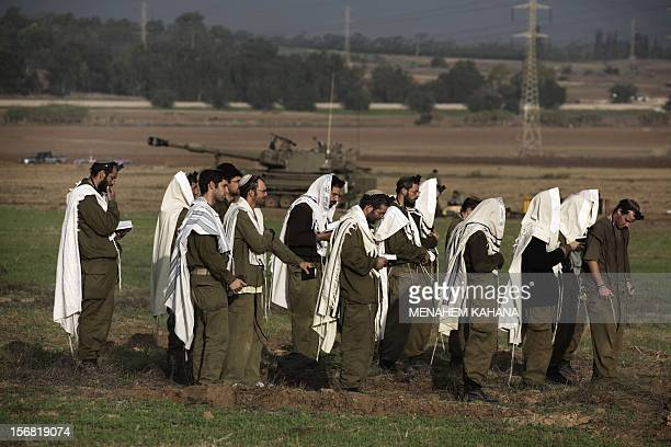 Israeli soldiers wearing 'Tallit' and 'Tefilin' perform morning prayers at an artillery battery deployment area near the IsraelGaza Strip border on...