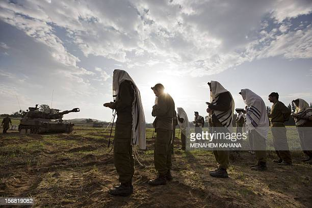 Israeli soldiers wearing Tallit and Tefilin perform morning prayers at an artillery battery deployment area near the IsraelGaza Strip border on...