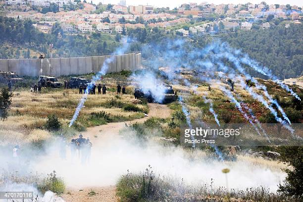 Israeli soldiers who stand by the separation wall in the West Bank village of Bil'in fire volleys of tear gas from an army jeep Palestinians across...