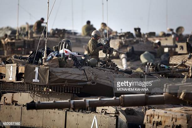 Israeli soldiers work on their Merkava tanks in an army deployment area near Israel's border with the Gaza Strip on July 12 2014 Israel pounded Gaza...
