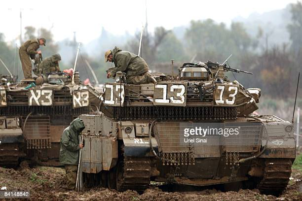 Israeli soldiers work on their tank as Israeli troops are deployed on December 31 2008 at the border between Israel and Gaza The Israeli conflict...