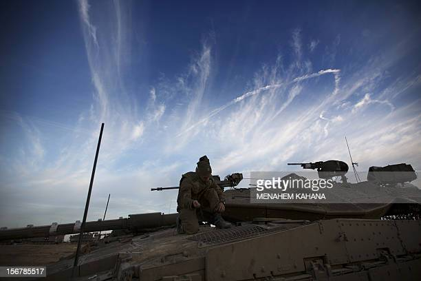 Israeli tanks are stationed at an Israeli army deployment area near the IsraelGaza Strip border with smoke trail in the background on November 21...