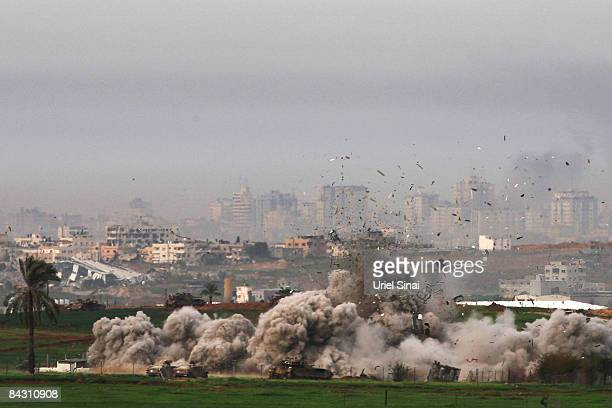 Israeli tanks destroy a house on January 16, 2009 in Gaza, seen from the Israeli side of the border. Yesterday saw an Israeli attack using white...
