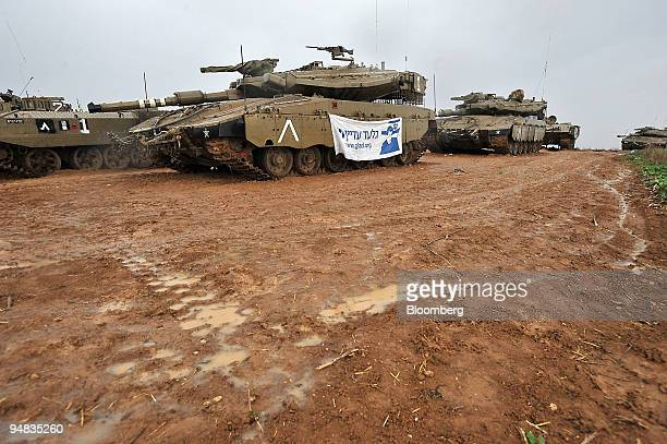Israeli tanks one with a poster showing kidnapped Israeli soldier Gilad Shalit sit parked in an area next to the IsraelGaza border on Wednesday Dec...