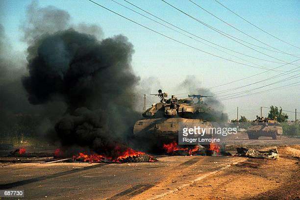 Israeli tanks roll over a makeshift barricade and enter deeper December 15, 2001 into Beit Hanoun, Gaza. Earlier in the day, Israeli forces made an...