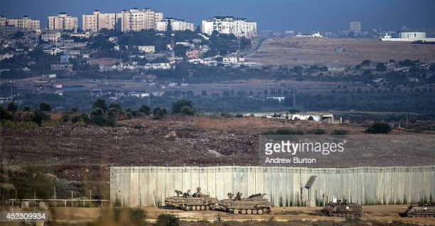 Israeli tanks sit positioned next to a gap in the wall seperating Gaza and Israel on the morning July 18 2014 near Sderot Israel Late last night the...