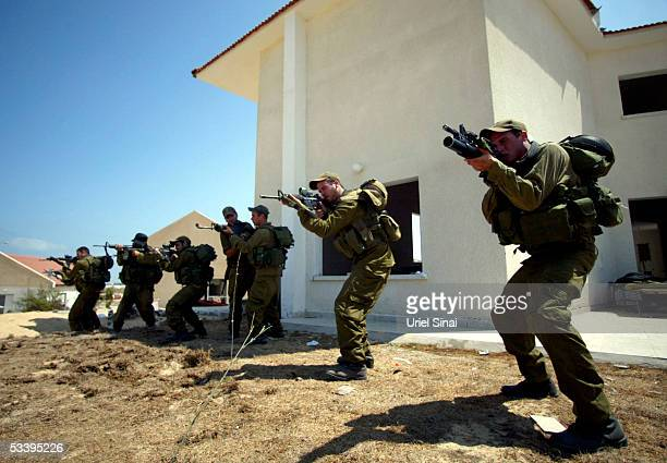 Israeli troops advance against Palestinian infiltrators during a training exercise August 16, 2005 in Pe'at Sadeh settlement in the Gaza Strip. The...
