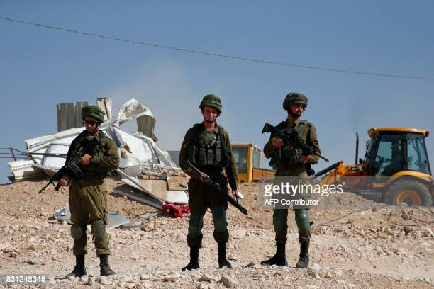 Israeli troops and bulldozers are seen as they demolish houses in the Palestinian bedouin village of Khashm alDaraj in the southern area of Yatta...