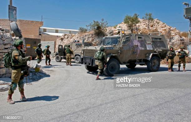 Israeli troops block a road during a house-to-house search operation in the West Bank village of Beit Fajjar near Bethlehem on August 8 following a...