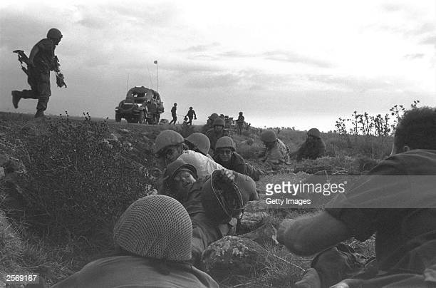Israeli troops dive for cover as Syrian warplanes strafe their column October 8 1973 on the Golan Heights two days into the Yom Kippur War Israeli...