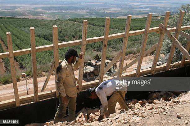 MOUSSAOUI Israeli troops drive their Humvee past Lebanese Muslim Shiite men constructing a wall in the southern village of Kfar Kila opposite the...
