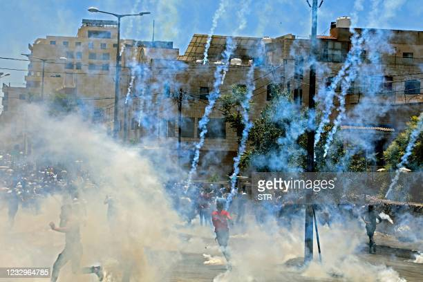 Israeli troops fire tear gas towards demonstrators during a protest against Israeli occupation in the West Bank biblical town of Bethlehem on May 18...