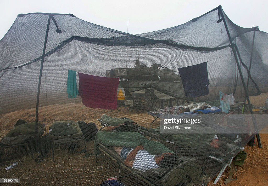 Israeli troops sleep in the morning mist under netting alongside their tank near the border with the Gaza Strip August 15, 2005 in the fields of Kibbutz Mefalsim in southern Israel. The Israeli army has deployed hundreds of tanks and armored vehicles and thousands of troops to defend the Jewish state's historic withdrawal from the Gaza Strip after a 38-year occupation.