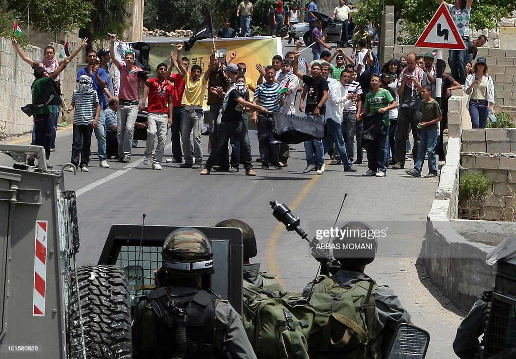 Israeli troops stand in position across Palestinian and foreign demonstrators in the West Bank village of Nabi Saleh on May 21, 2010 during a protest against settlement expansion. Israeli forces shot dead two Palestinian gunmen who had just infiltrated Israel from the Gaza Strip, the military said.