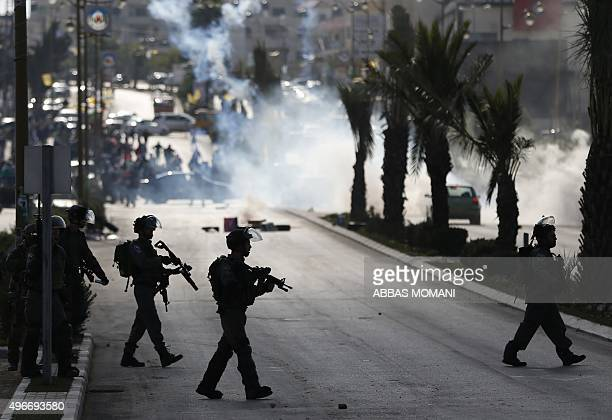 Israeli troops take position during clashes with Palestinian protestors at the entrance of the Palestinian town of alBireh on the outskirts of...
