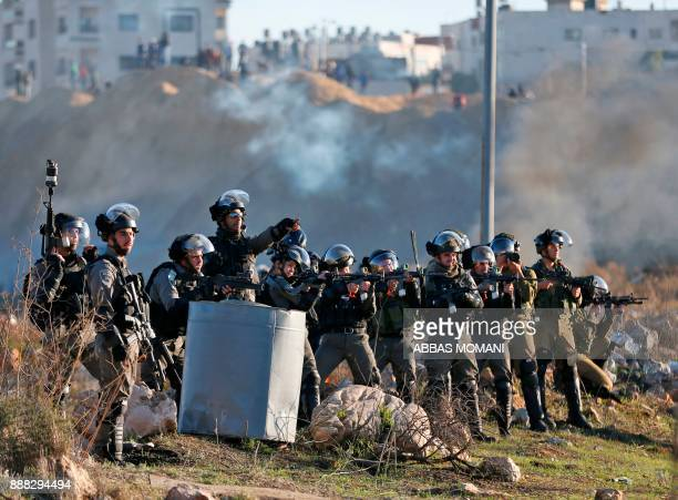 TOPSHOT Israeli troops take position during clashes with Palestinian protesters near an Israeli checkpoint in the West Bank city of Ramallah on...
