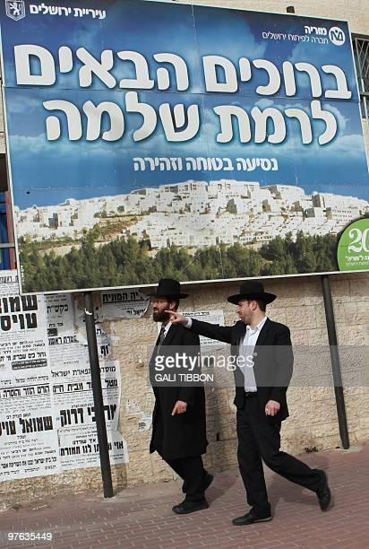 Israeli ultraOrthodox Jewish men walk past a sign with the image of the east Jerusalem settlement of Ramat Shlomo on March 11 2010 Israeli Prime...