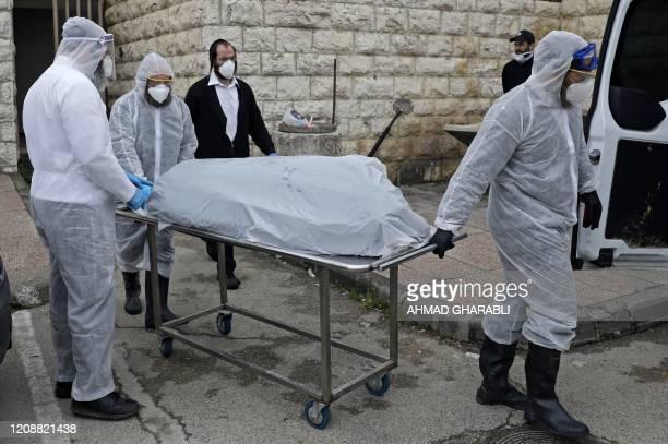 Israeli UltraOrthodox Jewish workers wearing protective equipment transport the body of a patient who died from complications of Coronavirus...