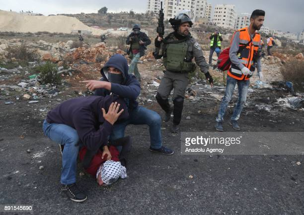 Israeli undercover police officers detain a protester as they intervene in a demonstration against US President Donald Trump's recognition of...