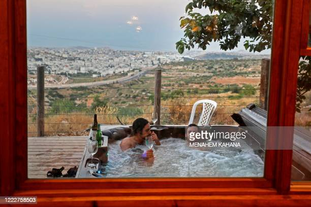 Israeli visitors are pictured in a jacuzzi as they come to the house of a friend living in the Israeli settlement of Sde Boaz located near the...
