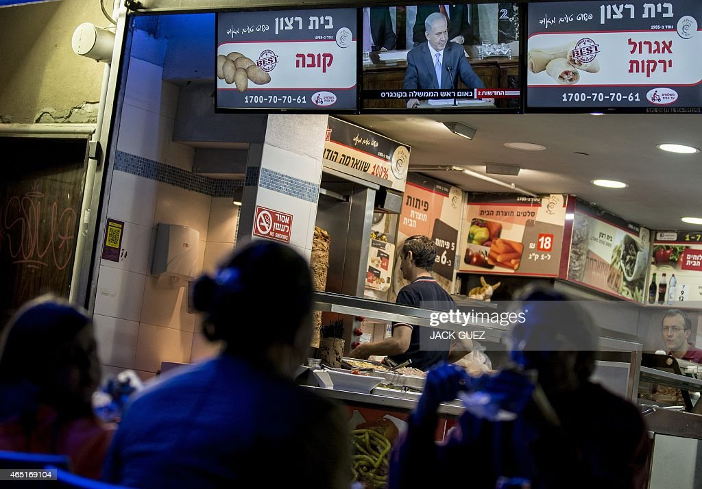 Israeli watch a television broadcast of Israeli Prime Minister Benjamin Netanyahu addressing the US Congress at the US Capitol in Washington, at a restaurant in the Israeli Mediterranean coastal city of Netanya on March 3, 2015. Netanyahu declared that the deal being negotiated between world powers and Iran would leave Tehran free to develop nuclear weapons.
