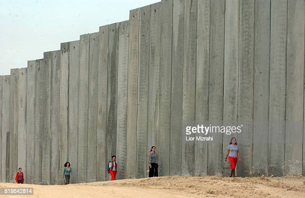 Israeli women model for a photo shoot at the separation barrier between the West Bank and Jerusalem in the East Jerusalem neighborhood of Atur...