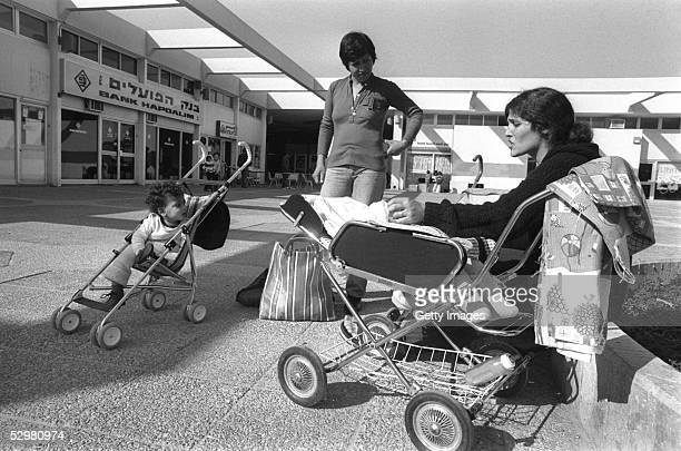 Israeli women settlers gather with heir babies in the commercial center December 10 1981 of the Israeli settlement of Yamit in the Sinai Desert just...