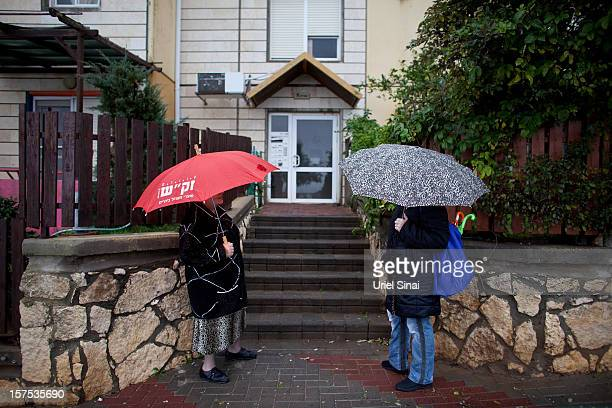Israeli women shelter under umbrellas on December 4 2012 in the West Bank Jewish settlement of Ariel Israel plans to build 3000 new settler homes in...