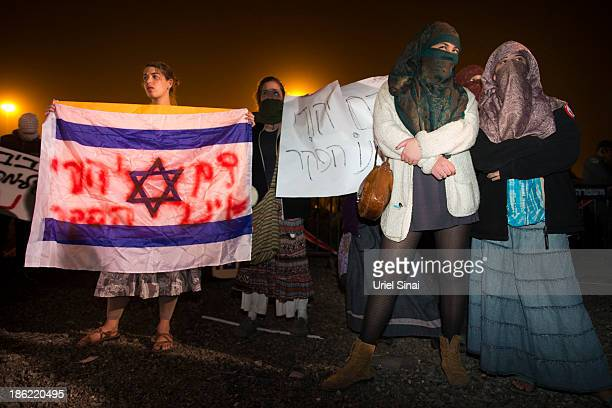 Israeli women wear traditional Palestinian scarfs as right wing Israelis demonstrate against the release of 26 Palestinian prisoners on October 29...