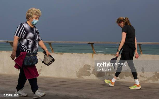 Israeli women wearing protective masks walk on the beach promenade on May 9, 2020 in Tel Aviv, Israel. Israel is preparing to reopen markets and...