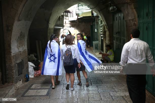 Israeli women with national flags walk inside Jerusalem's old city on June 5 2016 as they celebrate Jerusalem Day that marks the anniversary of the...