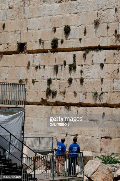 Israeli workers look at the place where a massive stone block dislodged from the Western Wall Judaism's holiest worship site falling down onto an...