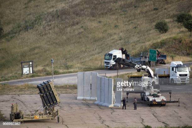 Israeli workers place concrete wall next to the Iron Dome defense system, designed to intercept and destroy incoming short-range rockets and...