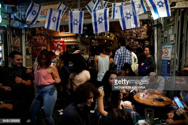 Israeli youths dance at the Mahane Yehuda market in the centre of Jerusalem late on April 18 2018 during the 70th Independence Day celebrations...