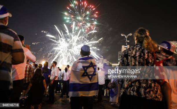 TOPSHOT Israeli youths dressed in memorabilia depicting the Israeli flag watch fireworks over the centre of Jerusalem late on April 18 during the...