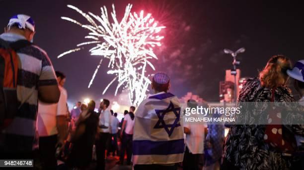 Israeli youths dressed in memorabilia depicting the Israeli flag watch fireworks over the centre of Jerusalem late on April 18 during the conclusion...