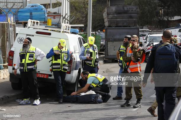 Israeli Zaka emergency services volunteers gather at the site of a reported attack at the Barkan Industrial Park near the Israeli settlement of Ariel...