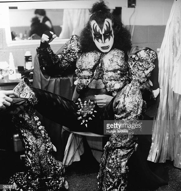 Israeliborn bass guitarist Gene Simmons of the rock band KISS sits in a dressing room wearing full makeup and costume and waves his fist circa 1977