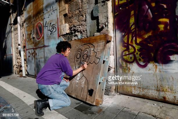 Israeliborn New Yorkbased street artist Sara Erenthal draws one of her emblematic woman's face in the Israeli coastal city of Tel Aviv on January 28...