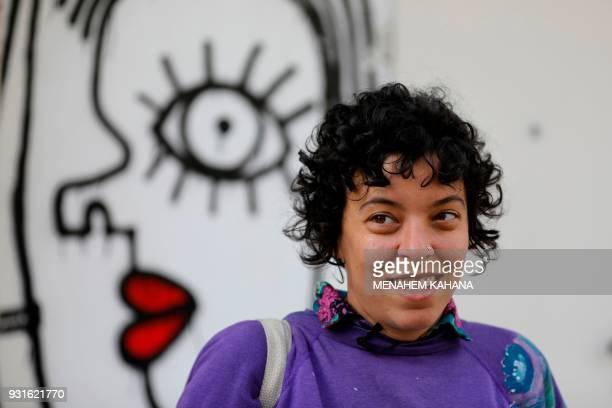 Israeliborn New Yorkbased street artist Sara Erenthal smiles in front of one of her murals in the Israeli coastal city of Tel Aviv on January 28 2018...