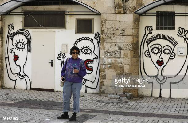 Israeliborn New Yorkbased street artist Sara Erenthal stands in front of one of her murals in the Israeli coastal city of Tel Aviv on January 28 2018...